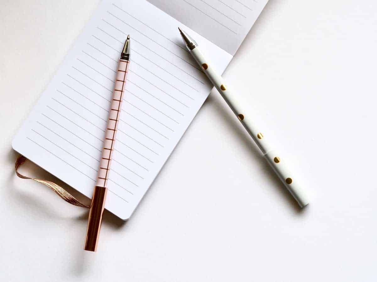 An notebook opened on a blank page with two pens lying on top