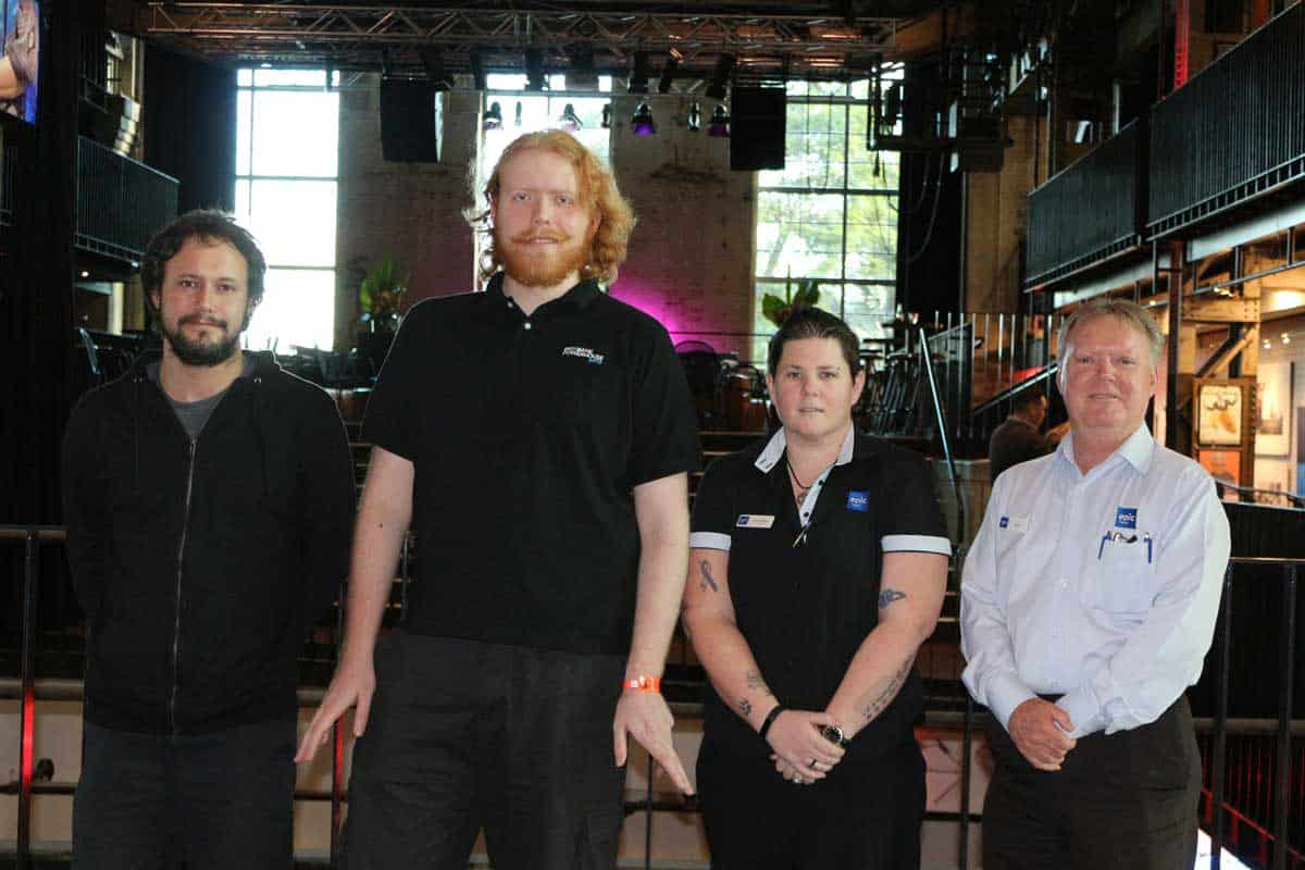 Alex with his co-wrokers at Brisbane Powerhouse and EPICs Sam, stand in front of a stage at Brisbane Powerhouse