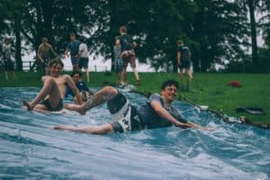 A gourp of young boys play on a slip and slide
