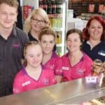 Elizabeth stands behind the counter with her team at Donut King
