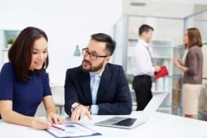 A business man and women sit at a desk and conduct a meeting