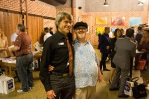 EPIC Assist's Disability Services Manager David Law with artist Peter Rowe standing among st the crowd at the exhibition