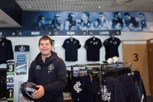 Dan holding a football inside the Football Club store.