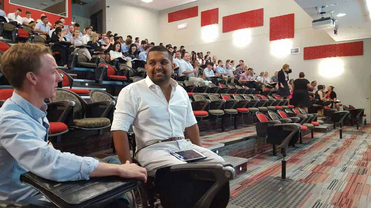 Dr Dinesh Palipana sits in a university lecture hall with his lecturer