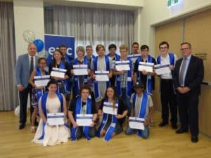 School Attending Trainees (SAT) from Outer North Brisbane with Luke Howarth MP and Mark Willis from CCIQ, holding their certificates and wearing their graduation gowns