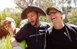 Two young men and a women, all wearing hats, laugh while they work in a garden