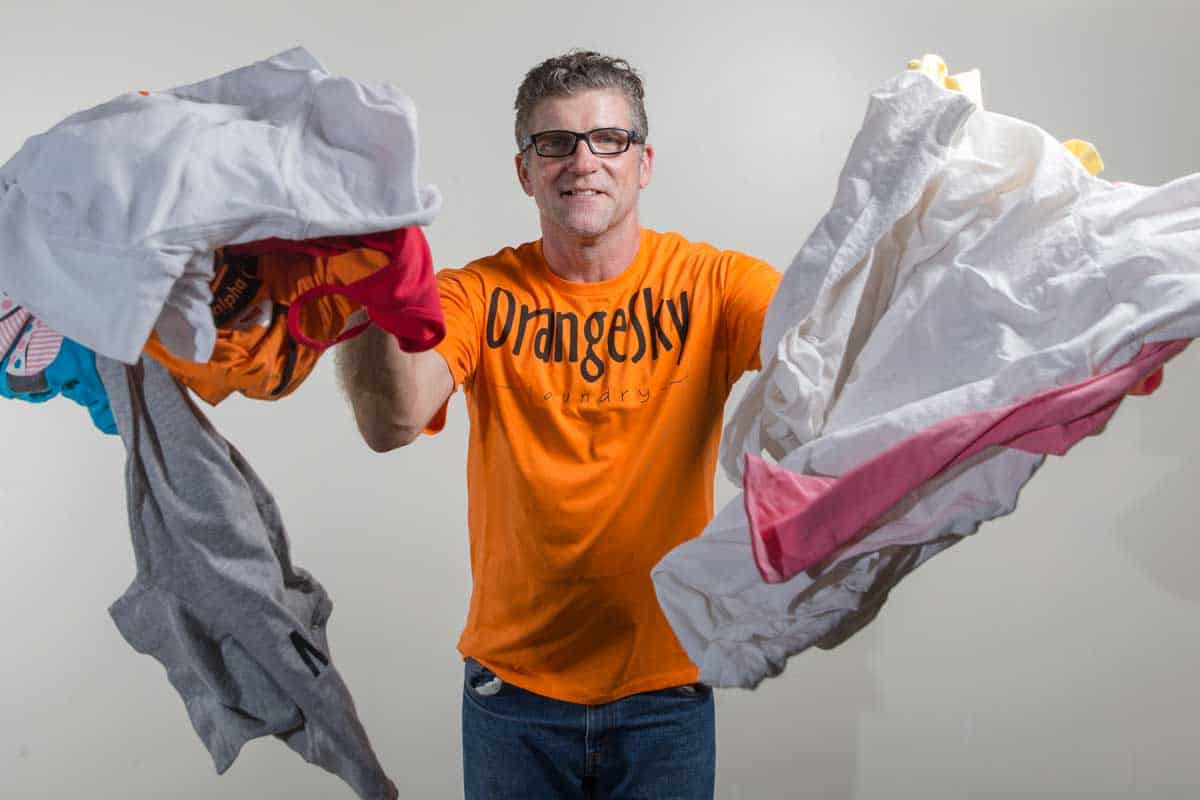 Orange Sky Laundry's friend on the street, Gavan, stands in a studio and throws clean clothes toward the camera