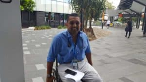 Dr Dinesh pictured out the front of Gold Coast University Hospital with a stethoscope around his neck