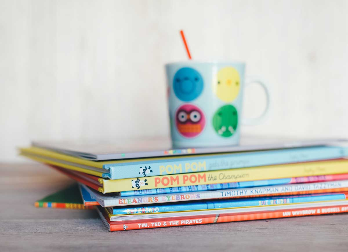 A stack of children's books sit on a desk