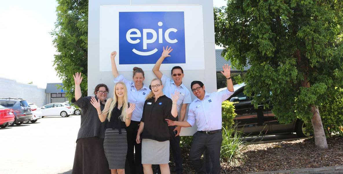 The EPIC Assist Logan team stand out the front of the EPIC Logan office with their arms raised in the air in celebration