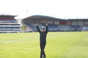 EPIC participant Dan walks across the football field at Carlton Rugby Club with his arms raised