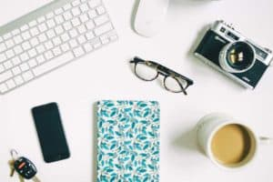 A desk with a laptop, glass, phone, notebook, coffee and camera