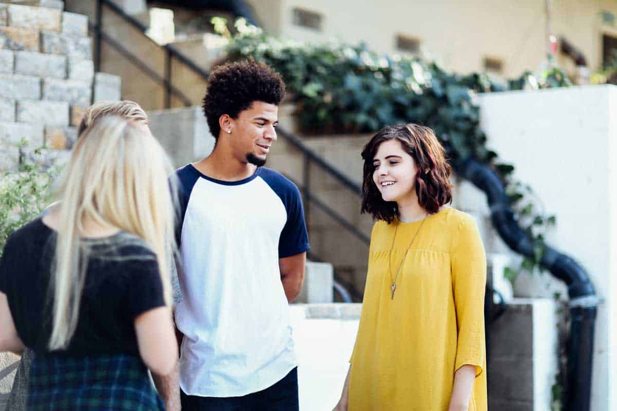 Two young women and a young man stand out the front of a university and have a conversation