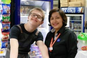 Julian with his EPIC Support Worker behind a kiosk counter