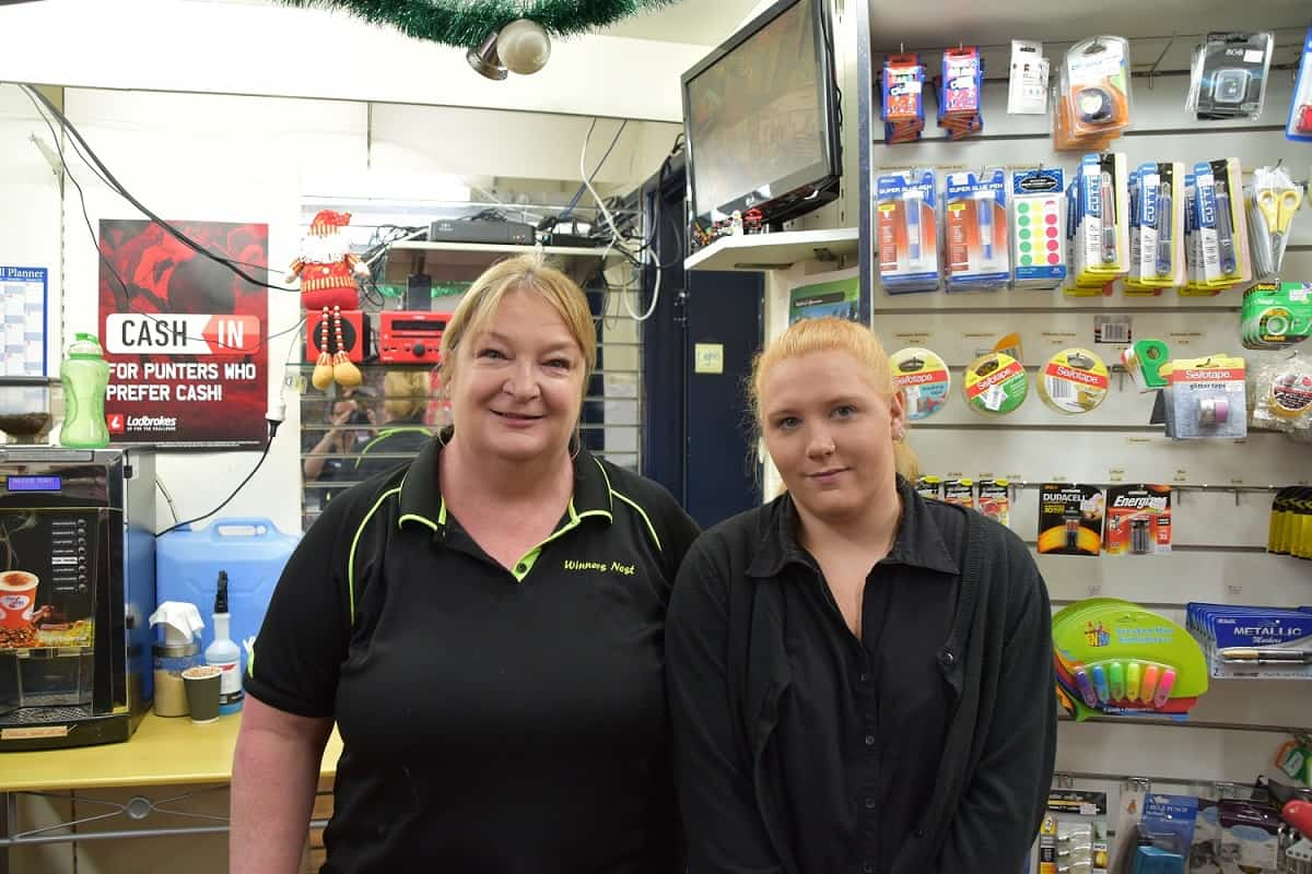 EPIC participant Sasha stands with her employer Lyn in front of the stationery section at the post office