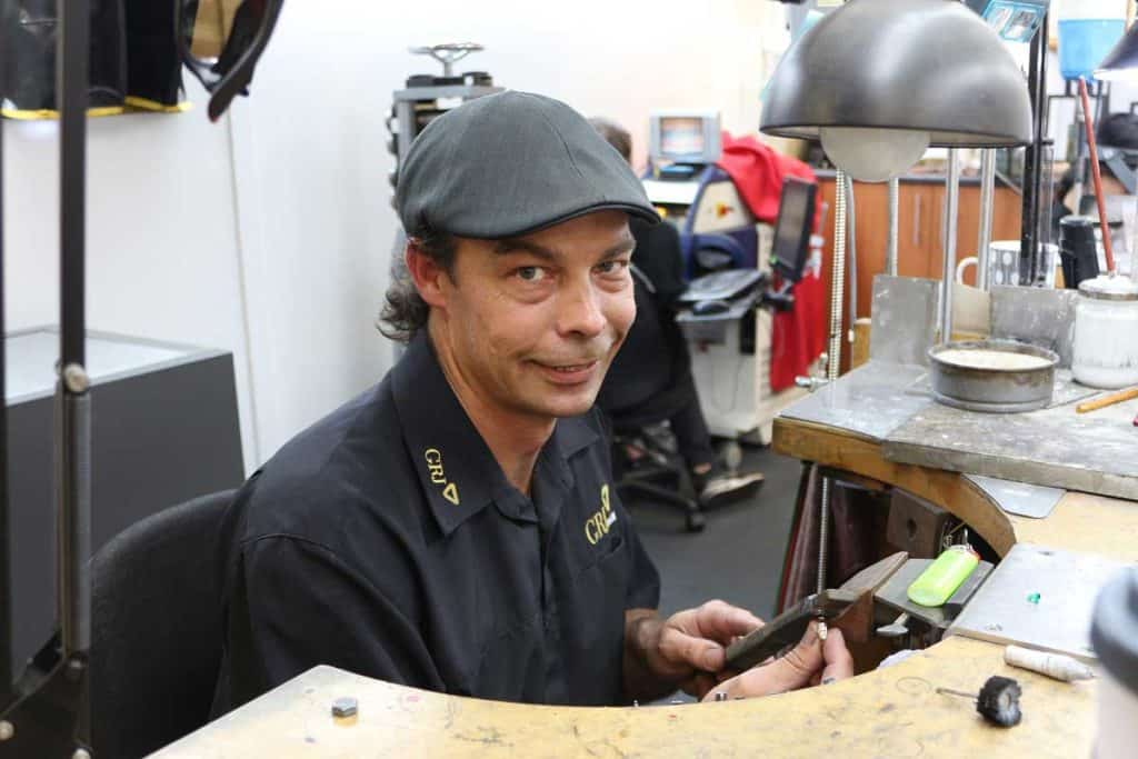 Mark sits behind his desk and works on a piece of jewellery