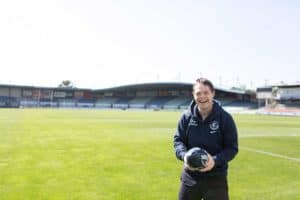 EPIC Assist participant Dan on the football field at Carlton Football Club holding a football