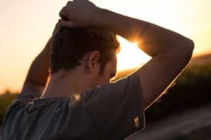 A man walks toward the sunset with his arms raised to his head and pulling at his hair
