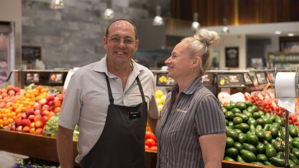 IGA Store Manager Belinda, stands with her EPIC employee Carl in front of the fruit and vegetable isle at IGA