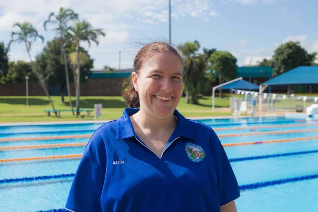 Erin stands in front of the Olympic length swimming pool at Bundy Swimming Academy