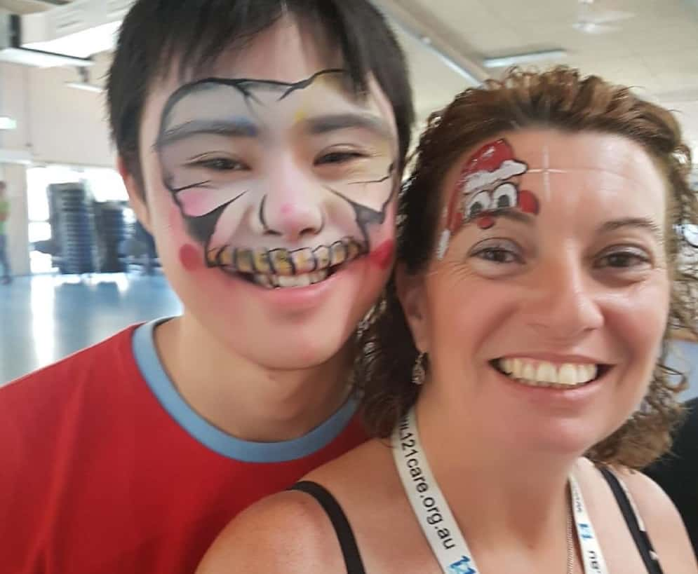 Lesley stands with one of the children she supports, with face paint on their faces.