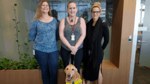 Jennea and her guide dog Ollie stand with her co-workers