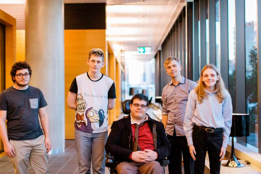 Five of our software testing participants stand in the hallway waiting to go into their course