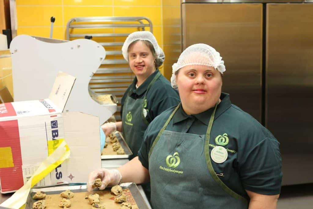 Two women with Down syndrome prepare cookies in the Woolworths bakery
