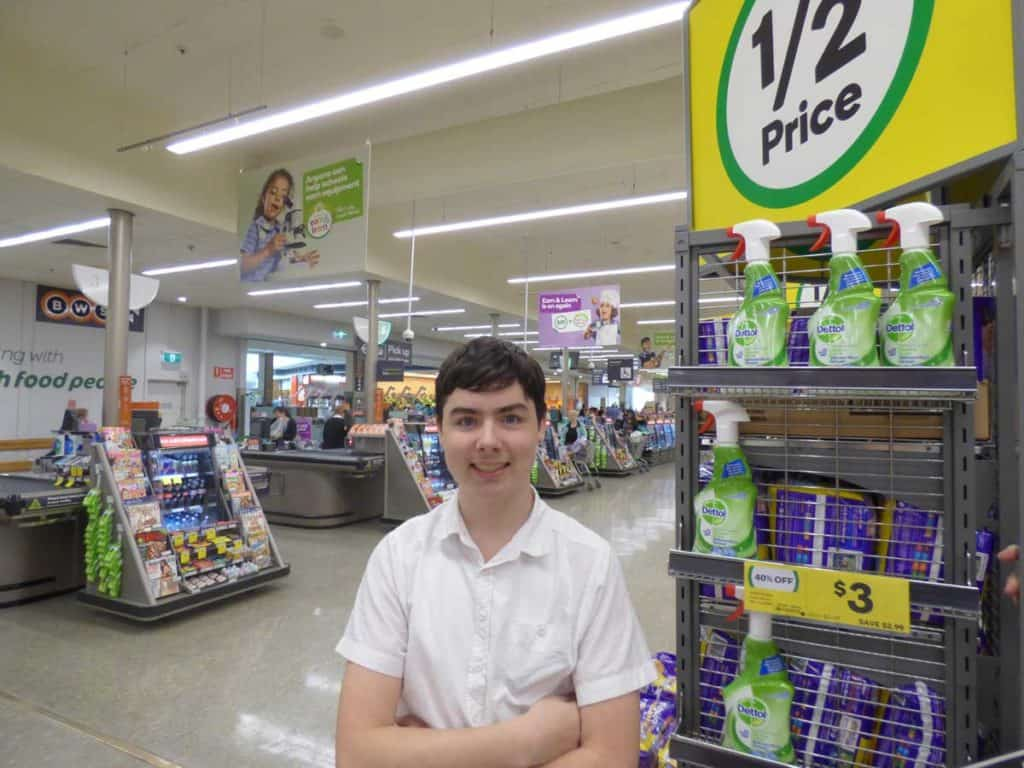 Lachlan stands in Woolworths with his hands folded in front of his chest