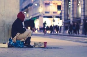 A homeless person sits on the street