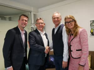 Bill Gamack shakes hands with the Thriving Now team