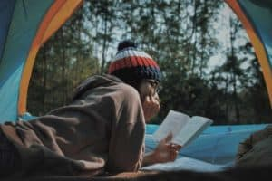 girl reads a book inside a camping tent