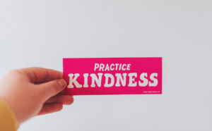 A hand holds up a pink note that reads 'practice kindness'