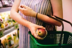 A woman puts a piece of fruit into her a green shopping basket