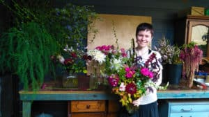 EPIC participant Ella stands beside a blue floristry table, holding a large bouquet of brightly coloured flowers