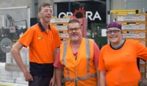Three workers in bright orange shirts pose together in a workshop