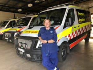 Bec stands, a paramedic, stands in front of an ambulance.