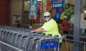 EPIC participant Joanne smiles while moving trolleys at her workplace