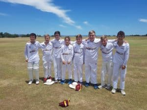 PBC Cricket Club team smiling proudly on the pitch