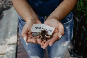 "A woman holding a handful of money and a note that says ""make a change."""