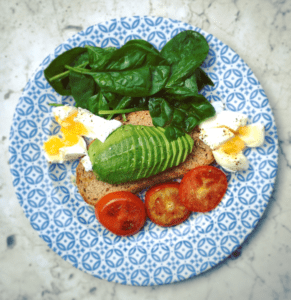 Aerial photo of a blue and white plate with bread, avocado, tomato, eggs and spinach