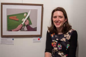 Steph smiles next to her artwork