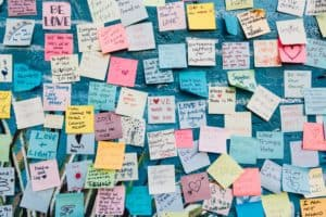 Board covered in colourful post-it notes with positive messages to help manage stress and anxiety when studying