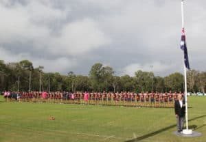 Noosa Tigers Australian Football Club lined up with the Australian flag.