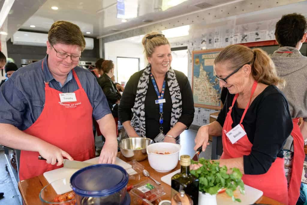 Two EPIC job seekers chop up food as an EPIC consultant watches