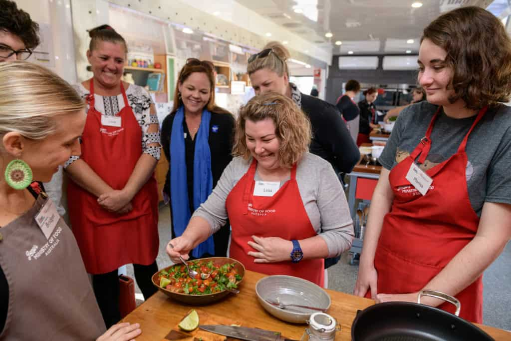 Leisa tries a tomato, while other job seekers watch.