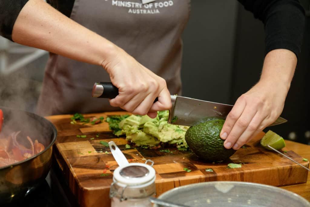 Someone chopping an avocado.