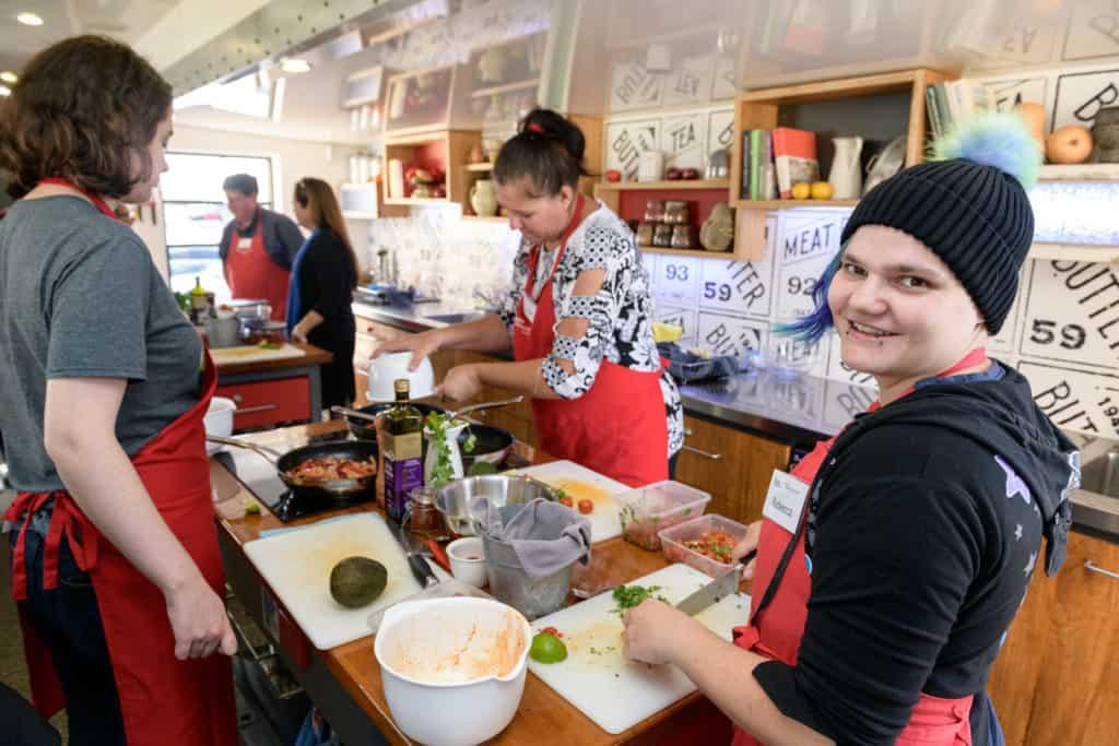 Three EPIC job seekers chop up food.