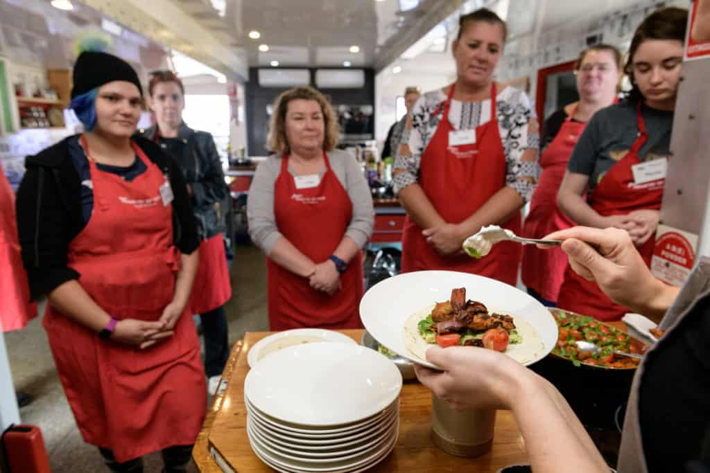 EPIC job seekers standing in a group as someone serves a fajita