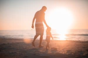 A father and daughter walking towards the ocean.